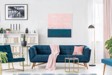 Soggiorno luminoso ed elegante con arredi blu rosa e oro