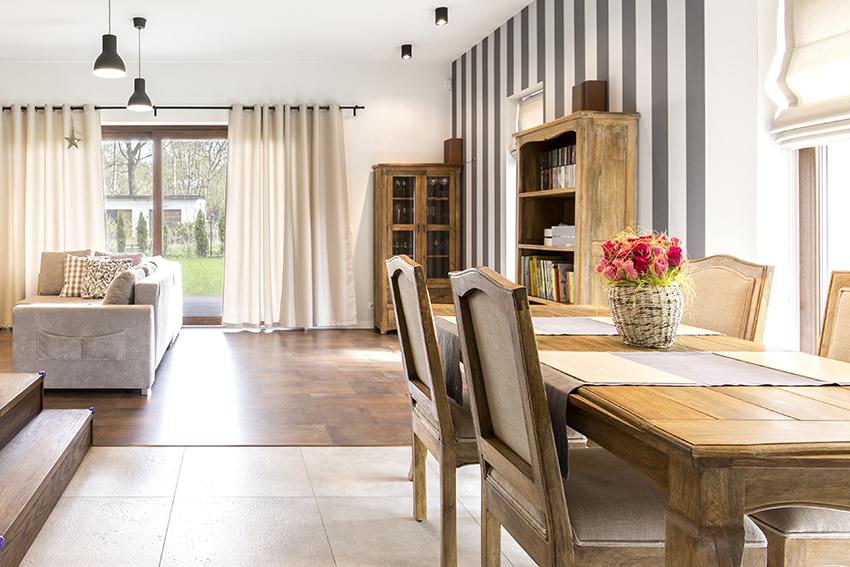 Soggiorno e sala da pranzo luminosi con ampie finestre, tende chiare e arredi in legno